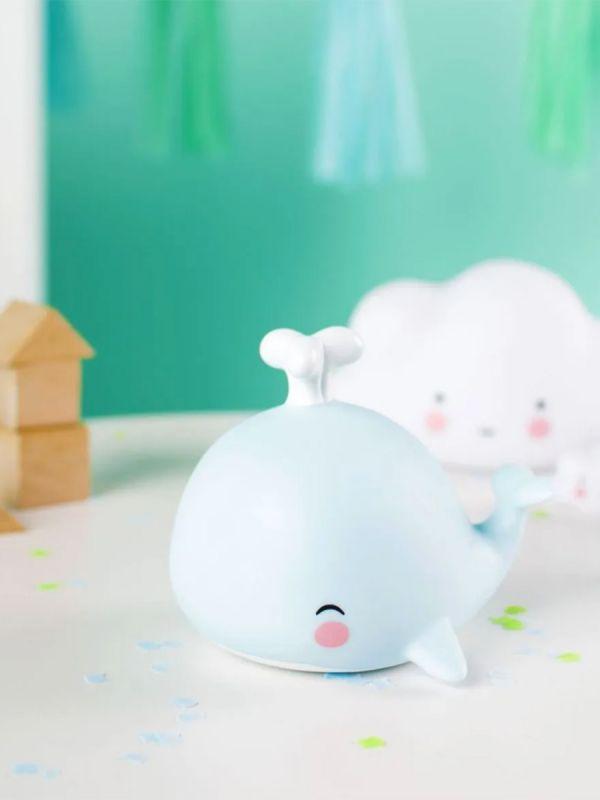 Pieni suloinen A little lovely company valaan poikanen on ihana yksityiskohta pienen yöpöydällä. Valo hehkuu pehmeästi ja auttaa lasta nukahtamaan.